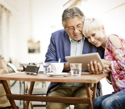 An older couple sitting a table while looking at a tablet device