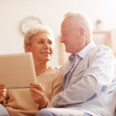 A couple smiling at one another while sitting on a couch holding a tablet device.