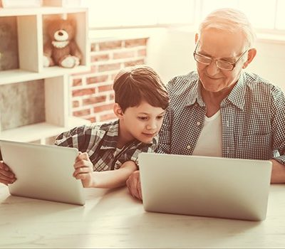 A grandfather and grandson looking at a laptop.