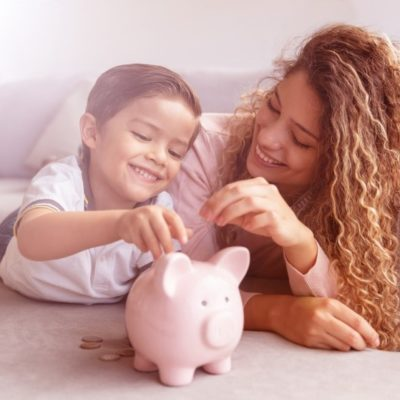 A mother and daughter putting loose change into a piggy bank.