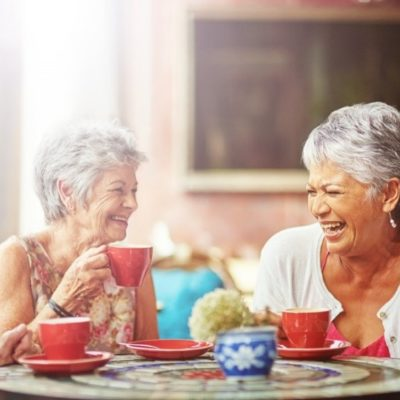 3 elderly women drinking coffee at a table while laughing
