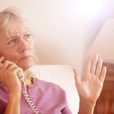An older woman talking on a telephone