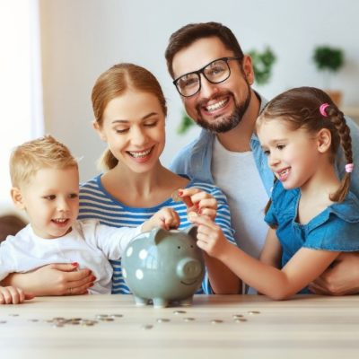 A family smiling while putting loose change into a piggy bank