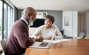 older couple reviewing paperwork and using laptop