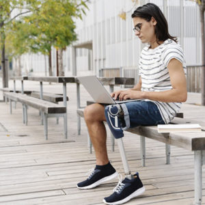 Contemplating man with artificial limb using laptop while sitting on bench in city