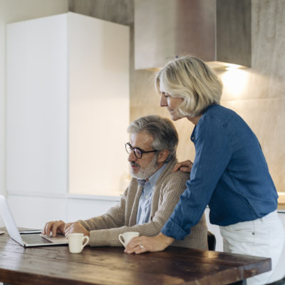 An elderly couple using a laptop while sitting at the kitchen table