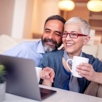 An older couple smiling and laughing while drinking coffee and using a laptop