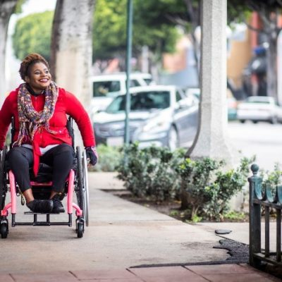 A woman strolling down the street in a wheelchair