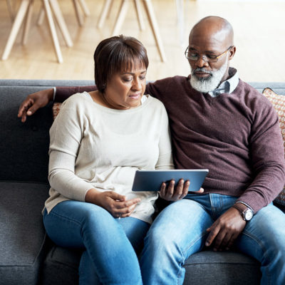 An older couple watching a video together on a tablet device.