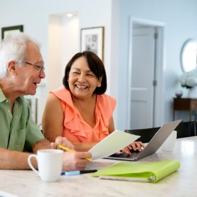 An eldery couple smiling at each other while reviewing finances on a laptop.