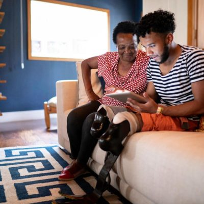 A mother and son sitting on a couch while looking at a tablet device
