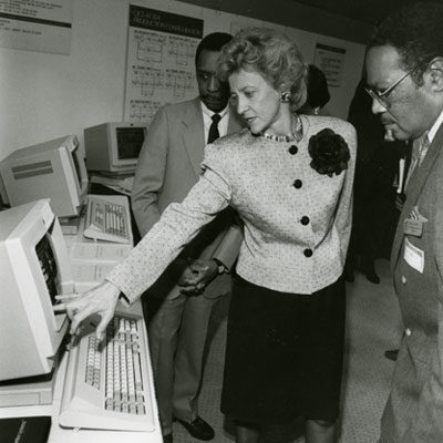 A photo of Dorcas Hardy and two gentlemen looking at a computer monitor.