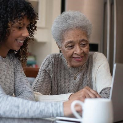 younger woman teaching older woman on laptop (for post)