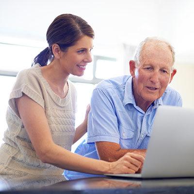 A senior man looking at something on his daughter's laptop