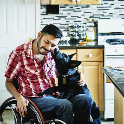 Smiling man in wheelchair having face licked by dog while hanging out in kitchen