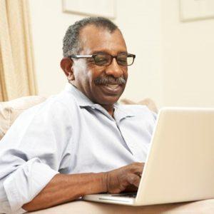 man searching internet on laptop computer
